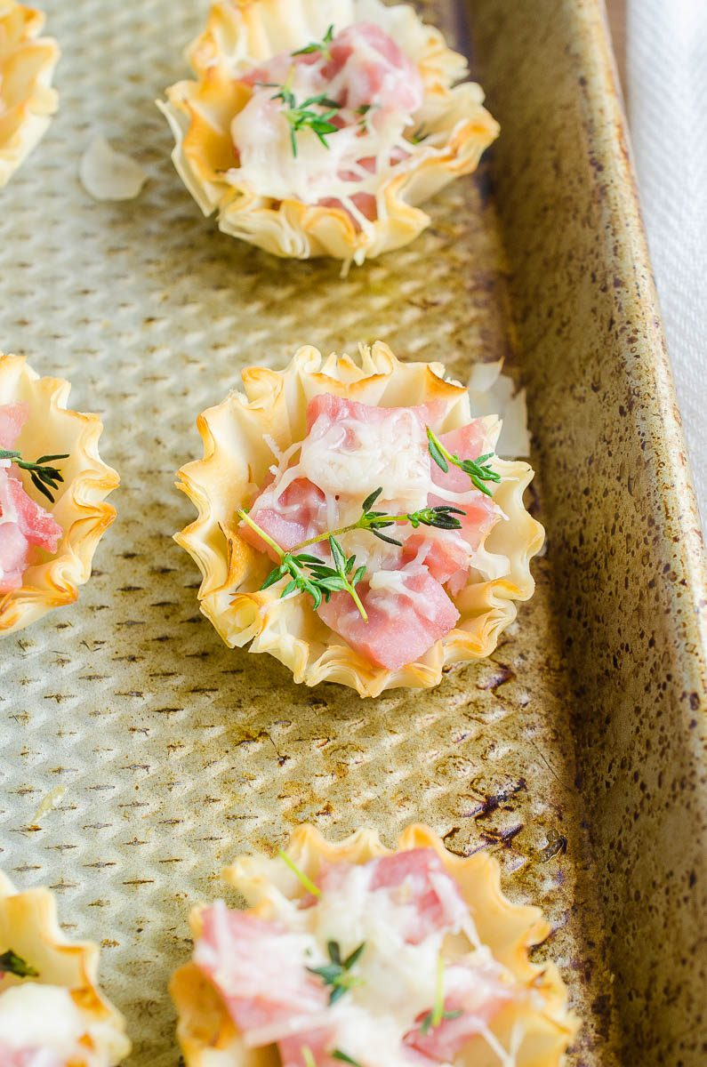 Ham and Gruyere in phyllo pastry cups on a baking sheet.