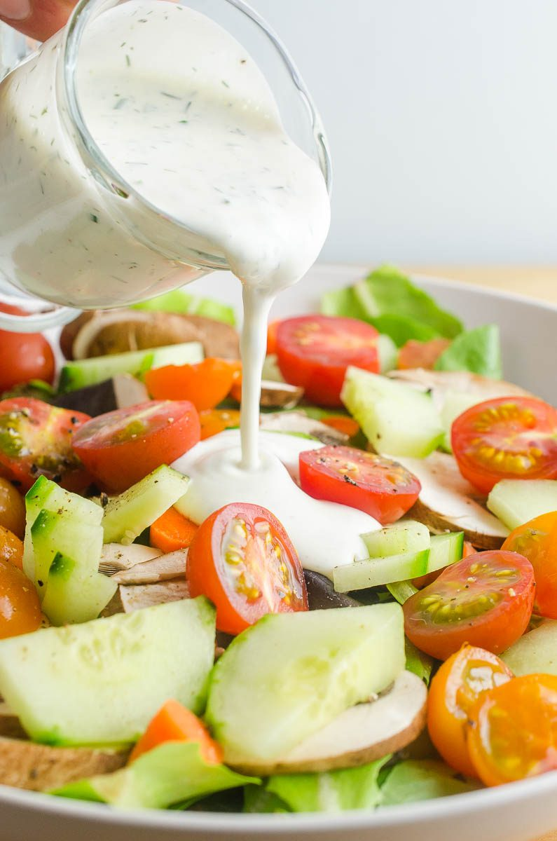 Pouring ranch dressing on a salad.
