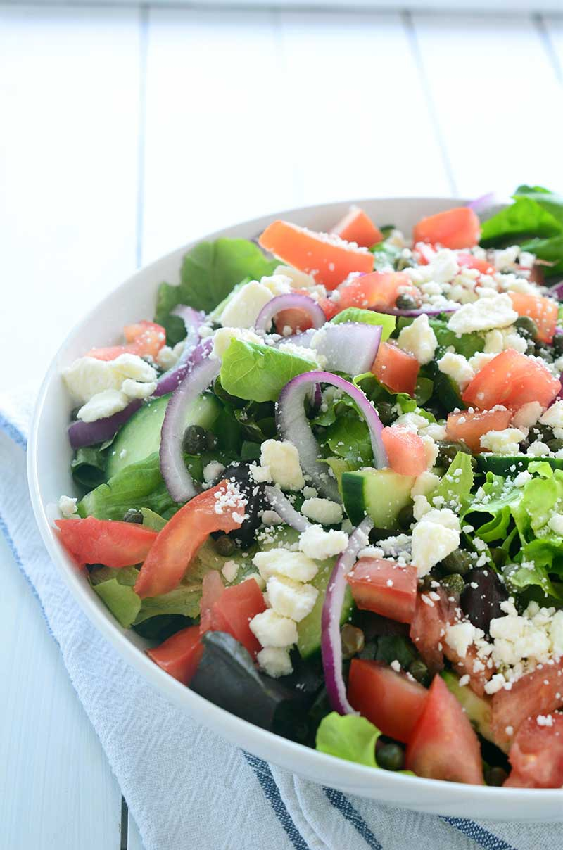 This Loaded Greek Salad has all kinds of goodies: olives, tomatoes, cucumbers, red onion, capers and feta and is tossed in a tangy Oregano vinaigrette.