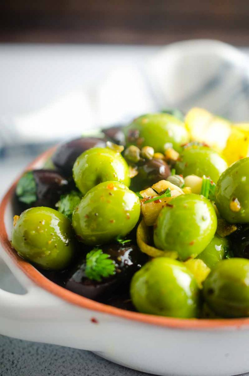 Easy Marinated Olives are a great addition to a cheese board or for holiday parties. A blend of olives, olive oil, garlic, capers and lemons make these the perfect party appetizer.
