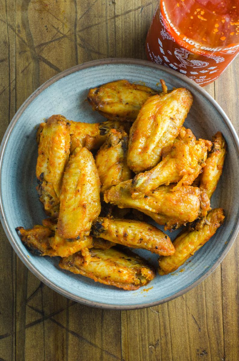 Sriracha Chicken Wings are baked to perfection and then tossed in a spicy sriracha sauce. They will be your new favorite chicken wing!