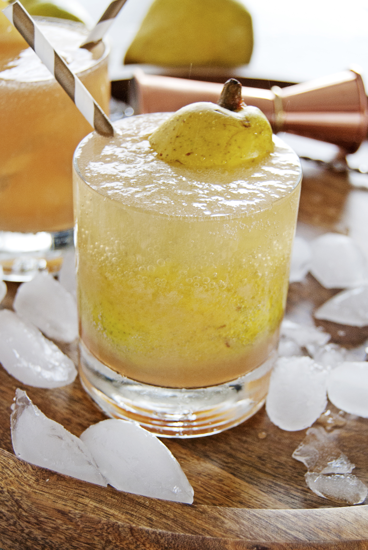 These cardamom pear spritzer cocktails feature delicious fresh pear juice, white rum, and a homemade honey cardamom simple syrup.