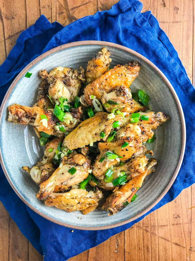 Baked Salt and Pepper Chicken wings are baked until crispy and tossed in a mixture of sesame oil, jalapeños, garlic and green onions.